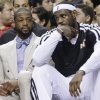 Photo - Miami Heat guard Dwyane Wade, left, and forward LeBron James sit on the bench during the first half of an NBA basketball game against the Portland Trail Blazers, Monday, March 24, 2014 in Miami. (AP Photo/Wilfredo Lee)