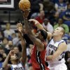 Miami Heat\'s LeBron James shoots as Minnesota Timberwolves\' Greg Stiemsma, right, and Mikael Gelabale, left, of France, defend in the first half of an NBA basketball game, Monday, March 4, 2013, in Minneapolis. (AP Photo/Jim Mone)