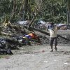 A resident covers his nose as he walks past typhoon Bopha\'s victims which are left unattended at New Bataan township, Compostela Valley in southern Philippines Saturday Dec. 8, 2012. Search and rescue operations following typhoon Bopha that killed nearly 600 people in the southern Philippines have been hampered in part because many residents of this ravaged farming community are too stunned to assist recovery efforts, an official said Saturday. (AP Photo/Bullit Marquez)