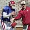 Photo - COLLEGE FOOTBALL: Oklahoma Sooner Offensive  Coordinator Chuck Long tries to knock the ball out of OU quarterback#18 Jason White's hands as the sooners go through drills during Saturday's spring practice at Memorial Stadium in Norman. Staff photo by Ty Russell.