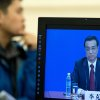 A man listens to a news conference by newly-appointed Premier Li Keqiang who appears on a monitor screen after the closing ceremony of the National People\'s Congress at the Great Hall of the People in Beijing Sunday, March 17, 2013. China\'s new leaders pledged to run a cleaner, more efficient government and slash spending on official perks Sunday as the ceremonial legislature wrapped up a pivotal session to install a new leadership in a once-a-decade transfer of power. (AP Photo/Andy Wong)