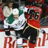 Dallas Stars\' Jordie Benn, left, is checked by Calgary Flames\' Brian McGrattan during first-period NHL hockey game action in Calgary, Alberta., Thursday, Nov. 14, 2013. (AP Photo/The Canadian Press, Jeff McIntosh)