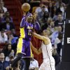 Photo - Los Angeles Lakers center Dwight Howard (12) passes past Miami Heat forward Shane Battier during the first half of an NBA basketball game, Sunday, Feb. 10, 2013, in Miami. (AP Photo/Wilfredo Lee)