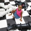 "Photo - ""Miracle"" child Jalesa plays on an oversized chess board at a Mariane's Rentals for Special Events music video shoot. Former patients, Miss Oklahoma and other pageant queens helped produce a video to benefit Children's Miracle Network Hospitals.  Photo by Jim Beckel,  The Oklahoman <strong>Jim Beckel - THE OKLAHOMAN</strong>"