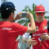 A fan takes a photo of Ferrari driver Kimi Raikkonen of Finland as he arrives at the paddock before the Malaysian Formula One Grand Prix at Sepang International Circuit in Sepang, Malaysia, Sunday, March 30, 2014. (AP Photo/Peter Lim)