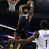 Photo - Miami Heat forward LeBron James (6) dunks the ball over New Orleans Pelicans forward Tyreke Evans (1) and New Orleans Pelicans forward Anthony Davis, left, during the first half of an NBA basketball game in New Orleans, Saturday, March 22, 2014. (AP Photo/Jonathan Bachman)