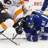 Toronto Maple Leafs\' Korbinian Holzer (55) and Philadelphia Flyers\' Mike Knuble (9) battle for the puck during the first period of their NHL hockey game, Monday, Feb. 11, 2013, in Toronto. (AP Photo/The Canadian Press, Chris Young)