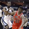Photo - Memphis Grizzlies' Tony Allen, left, defends against Chicago Bulls' Jimmy Butler (21) in the first half of an NBA basketball game in Memphis, Tenn., Monday, Dec. 30, 2013. (AP Photo/Danny Johnston)