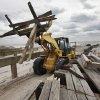 A front-end loader carries scraps of timber as it dismantles the storm-damaged boardwalk in Long Beach, N.Y., Friday, Feb. 1, 2013. Three months after Superstorm Sandy devastated the coastal areas of New Jersey and New York, Congress finally passed a $50.5 billion bill to rebuild homes, businesses, utilities, mass transit and other critical infrastructure. (AP Photo/Mark Lennihan)