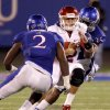 Oklahoma\'s Landry Jones (12) is brought down between Kansas\' Darius Willis (2) and Toben Opurum (35) during the college football game between the University of Oklahoma Sooners (OU) and the University of Kansas Jayhawks (KU) at Memorial Stadium in Lawrence, Kansas, Saturday, Oct. 15, 2011. Photo by Bryan Terry, The Oklahoman