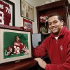 Jordan Evans with a portrait of him, at age three, wearing his dad\'s jersey from his playing days at the University of Oklahoma. The photo hangs in the office of Jordan\'s dad, former OU football player, Scott Evans. The framed photo was given to Scott and to his dad as a gift. Photo by Jim Beckel, The Oklahoman