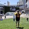 A Tony Gwynn fan shoots a photo of the big screen outside Petco Park that displays images of Gwynn who passed away Monday, June 16, 2014, in San Diego. Gwynn, an eight time National League batting champion with the San Diego Padres and a member of Baseball Hall of Fame, died Monday from cancer. He was 54. (AP Photo/Lenny Ignelzi)