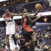 Photo - Toronto Raptors Amir Johnson (15) drives the ball and scores against Washington Wizards Martell Webster (9), during the first half of an NBA basketball game in Washington, Tuesday, Feb. 18, 2014. (AP Photo/Manuel Balce Ceneta)