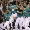 Photo -   Seattle Mariners' Munenori Kawasaki (61) is mobbed by teammates after he scored the winning run against the Detroit Tigers in a baseball game, Monday, May 7, 2012, in Seattle. The Mariners beat the Tigers, 3-2. (AP Photo/Ted S. Warren)