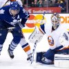 Photo - Toronto Maple Leafs forward Joffrey Lupul, left, battles for the lose puck against New York Islanders goalie Kevin Poulin, right, during second period of an NHL hockey game in Toronto, Tuesday, Jan. 7, 2014. (AP Photo/The Canadian Press, Nathan Denette)