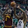Photo - Cleveland Cavaliers C.J. Miles, left, shoots the ball past Utah Jazz's Derrick Favors during the first half of an NBA basketball game in Salt Lake City, Friday, Jan. 10, 2014. (AP photo/George Frey)