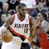 Photo - Portland Trail Blazers forward LaMarcus Aldridge, left, drives on Toronto Raptors forward Amir Johnson during the first half of an NBA basketball game in Portland, Ore., Saturday, Feb. 1, 2014. (AP Photo/Don Ryan)