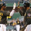 Photo - Pittsburgh Pirates' Andrew McCutchen (22) is greeted by teammate Starling Marte as he crosses home plate after hitting a two-run home run off Milwaukee Brewers starting pitcher Yovani Gallardo during the first inning of a baseball game in Pittsburgh, Thursday, April 17, 2014. (AP Photo/Gene J. Puskar)