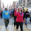 Photo - Boston Marathon bombing survivor Heather Abbott carries a symbolic torch as she crosses the marathon finish line in Boston, Sunday, April 13, 2014,  for the last leg of a cross country charity run that began in March in California. Abbott, along with other survivors and family members joined the relay runners for the final half-block to the finish. (AP Photo/Michael Dwyer)