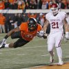 OSU\'s Jeremy Smith (31) flies into the end zone for a touchdown past OU\'s Tom Wort (21) in the first quarter during the Bedlam college football game between the Oklahoma State University Cowboys (OSU) and the University of Oklahoma Sooners (OU) at Boone Pickens Stadium in Stillwater, Okla., Saturday, Dec. 3, 2011. Photo by Nate Billings, The Oklahoman