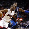 Miami Heat\'s Dwyane Wade (3) drives around Dallas Mavericks\' O.J. Mayo (32) during the first half of an NBA basketball game in Miami, Wednesday, Jan. 2, 2013. (AP Photo/J Pat Carter)