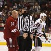 Phoenix Coyotes\' Raffi Torres (37) and Jamal Mayers (22) are taken to the penalty box by linesmen John Grandt (98) and Shane Heyer after fighting during the first period in an NHL hockey game Thursday, Feb. 7, 2013, in Glendale, Ariz.(AP Photo/Ross D. Franklin)
