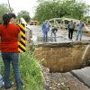 Photo - STORM, AFTERMATH, FLOOD, FLOODING: An unidentified couple stands on one side of SE 17 between Central and Robinson and look at gap between road surface and bridge that was created when roadbed was washed away by rushing waters of Lightning Creek after heavy rains and high winds created damage in various sections of Oklahoma City Monday, May 7, 2007.  Standing on the bridge surveying the damage are contractors and engineers.   By Jim Beckel,  The Oklahoman.  ORG XMIT: KOD
