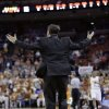 Photo - Oklahoma State coach Travis Ford jumps as he yells to his players during the first half on an NCAA college basketball game against Texas, Tuesday,  Feb. 11, 2014, in Austin, Texas. (AP Photo/Eric Gay)