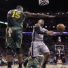Photo - San Antonio Spurs' Patty Mills, right, of Australia, shoots around Utah Jazz's Derrick Favors (15) during the first half of an NBA basketball game, Sunday, March 16, 2014, in San Antonio. (AP Photo/Eric Gay)