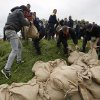 People build a sandbag dam by the bank of the Sava river in Sremska Mitrovica, 90 kilometers west of Belgrade, Serbia, Saturday, May 17, 2014. Record flooding in the Balkans leaves at least 20 people dead in Serbia and Bosnia and is forcing tens of thousands to flee their homes. Meteorologists say the flooding is the worst since records began 120 years ago. (AP Photo/Darko Vojinovic)