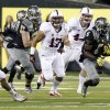 Oregon running back De\'Anthony Thomas, right, breaks into the open field ahead of Stanford defenders, from left,Shayne Skov, A. J. Tarpley and Chase Thomas during the first half of their NCAA college football game in Eugene, Ore., Saturday, Nov. 17, 2012.(AP Photo/Don Ryan)