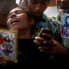 A woman mourns as she arrived in hopes to find her sister, seen in the photograph she is holding, among unclaimed bodies brought to a cemetery from the garment factory building collapse in preparation for a mass burial on Wednesday May 1, 2013 in Dhaka, Bangladesh. Several hundred people attended a mass funeral in a Dhaka suburb for 18 unidentified workers who died in the building collapse last week last week in the country\'s worst industrial disaster, killing at least 402 people and injuring 2,500. The bodies, rotting in the spring heat, were brought to the graveyard on the back of a flatbed truck.(AP Photo/Wong Maye-E)