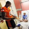 Oklahoma State wide receiver Tracy Moore gives Ernest Cobb, 9, an OSU pack during a visit by OSU football players to The Children\'s Hospital in Oklahoma City, Wednesday, July 11, 2012. Cobb is a patient at The Children\'s Hospital. Photo by Nate Billings, The Oklahoman