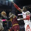Photo - Cleveland Cavaliers' Kyrie Irving, left, passes the ball away from Houston Rockets' Dwight Howard (12) in the first half of an NBA basketball game Saturday, Feb. 1, 2014, in Houston. (AP Photo/Pat Sullivan)