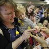 Darian Webb and son Eli, 2, inspect an Emperor Scorpion held by Adrina Shufran during