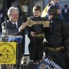 """Miles Scott, dressed as Batkid, stands next to Batman as he receives the key to the city from San Francisco Mayor Ed Lee, left, at a rally outside of City Hall in San Francisco, Friday, Nov. 15, 2013. Scott was called into service on Friday morning by San Francisco Police Chief Greg Suhr to help fight crime, as San Francisco turned into Gotham City as city officials helped fulfill the 5-year-old leukemia patient\'s wish to be """"Batkid,"""" The Greater Bay Area Make-A-Wish Foundation says. (AP Photo/Jeff Chiu)"""