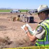 Photo - California Highway Patrol officer Kevin Long takes notes at the scene of a fatal accident in Blythe, California on Wednesday, May 21, 2014.  A tractor-trailer spilled a load of steel pipes onto a highway, triggering a bus crash Wednesday that killed four people and seriously injured several others on the main road linking Southern California and Arizona, authorities said. (AP Photo/Brian Skoloff)