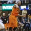 Photo - Oklahoma State's Markel Brown (22) celebrates after scoring during the first half of an NCAA college basketball game in Morgantown, W.Va., on Saturday, Feb. 23, 2013. (AP Photo/David Smith)