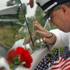 A U.S. Coast Guard Lieutenant who asked that his name not be used, kneels near his father\'s name after a remembrance ceremony at the Garden of Reflection Sunday, Sept. 11, 2011 in Yardley, Pa. The memorial honors nine people from Lower Makefield Township, where the memorial is located, eighteen people from Bucks County, and all 58 people from Pennsylvania that lost their lives in the attacks Sept. 11, 2001. (AP Photo/Alex Brandon)