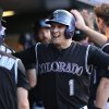 Colorado Rockies\' Corey Dickerson, left, congratulates Brandon Barnes after his two-run home run against the Miami Marlins in the third inning of a baseball game in Denver on Saturday, Aug. 23, 2014. (AP Photo/David Zalubowski)