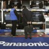 Photo - In this Thursday, Jan. 31, 2013 photo, a shopper speaks with a salesclerk in front of Panasonic flat-panel TVs at an electronics store in Tokyo. Japanese electronics maker Panasonic Corp. returned to the black last quarter as cost cuts and a weaker yen offset sliding sales. Panasonic is among the Japanese electronics makers battered by price plunges in gadgets and hot competition from more successful rivals such as U.S. manufacturer Apple Inc. and Samsung Electronics Co. of South Korea. Osaka-based Panasonic reported a 61.4 billion yen ($667 million) profit for the October-December period Friday, Feb. 1. (AP Photo/Shizuo Kambayashi)