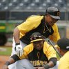 Photo - Pittsburgh Pirates' Gregory Polanco, bottom, is welcomed by Pittsburgh Pirates starting pitcher Edinson Volquez as he  stretches during warm ups before a baseball game against the Chicago Cubs in Pittsburgh Tuesday, June 10, 2014. It will be Polanco's Major League debut. (AP Photo/Gene J. Puskar)