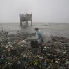 A Filipino man scavenges recyclable materials by the bay as strong winds and rains caused by Typhoon Koppu hit the coastal town of Navotas, north of Manila, Philippines on Sunday, Oct. 18, 2015. Slow-moving Typhoon Koppu blew ashore with fierce wind in the northeastern Philippines early Sunday, toppling trees and knocking out power and communications. (AP Photo/Aaron Favila)