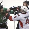 Photo - Ottawa Senators defenseman Chris Phillips (4) tangles with Dallas Stars left wing Antoine Roussel (21) as linesman Jay Sharrers tries to break it up during the second period an NHL Hockey game, Saturday, March 22, 2014, in Dallas. (AP Photo/LM Otero)