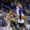 Photo - Indiana Pacers' George Hill, center, passes the ball as he is caught between Orlando Magic's Arron Afflalo, left, and Jameer Nelson, right, during the first half of an NBA basketball game in Orlando, Fla., Sunday, Feb. 9, 2014. (AP Photo/John Raoux)
