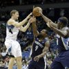 Minnesota Timberwolves\' Luke Ridnour, left, makes a pass over Memphis Grizzlies\' Tony Allen and Zach Randolph, right, in the first quarter of an NBA basketball game on Saturday, March 30, 2013, in Minneapolis. (AP Photo/Jim Mone)