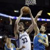 Photo - Memphis Grizzlies' Marc Gasol (33), of Spain, goes up between New Orleans Hornets' Austin Rivers, left, and Ryan Anderson, right, during the first half of an NBA basketball game in Memphis, Tenn., Sunday, Jan. 27, 2013. (AP Photo/Danny Johnston)