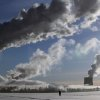 Men walk in snow covered field as smoke from a heating plant is seen on a winter\'s morning in Minsk, Belarus, Wednesday, Jan. 23, 2013. Temperatures of minus 14 degree Celsius (minus 6.8 degree Fahrenheit) hit the Belarusian capital. (AP Photo/Sergei Grits)