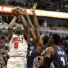 Photo - Chicago Bulls' Luol Deng (9), of South Sudan, goes up for a shot against against Charlotte Bobcats' Michael Kidd-Gilchrist (14), and Jeff Adrien (4), during the second quarter of an NBA basketball game in Chicago, Monday, Nov. 18, 2013. (AP Photo/Paul Beaty)