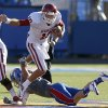 OU\'s Blake Bell (10) leaps over KU\'s Jake Love (57) during the college football game between the University of Oklahoma Sooners (OU) and the University of Kansas Jayhawks (KU) at Memorial Stadium in Lawrence, Kan., Saturday, Oct. 19, 2013. Oklahoma won 34-19. Photo by Bryan Terry, The Oklahoman
